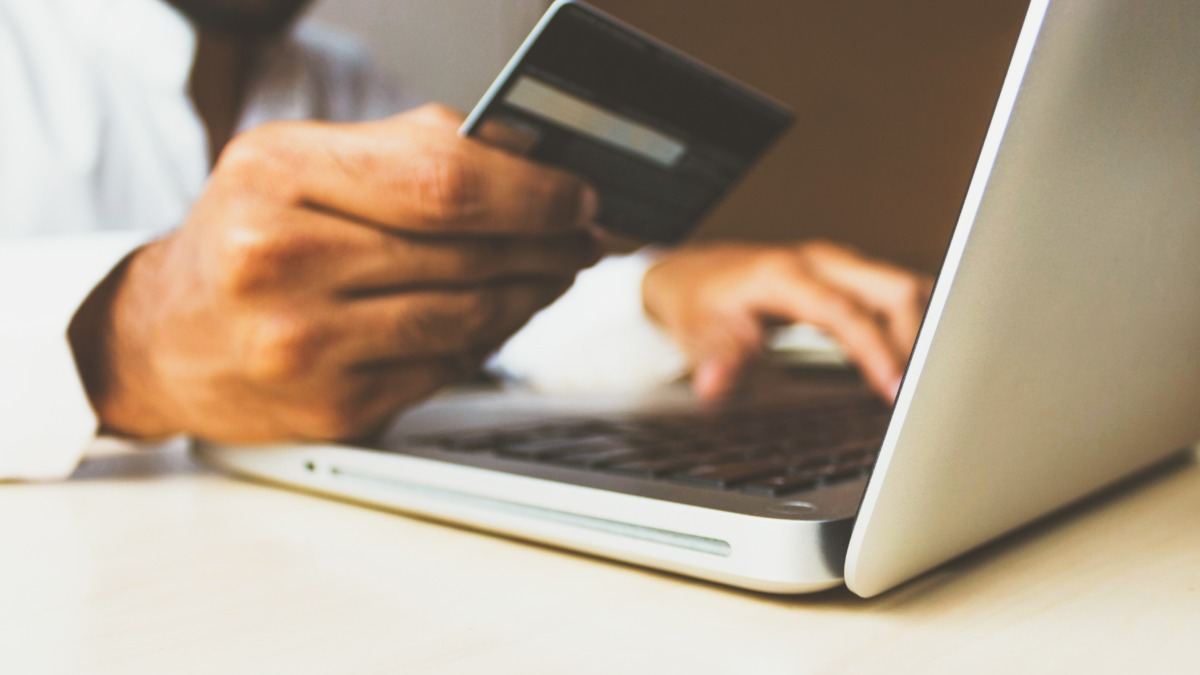 Customer in front of a laptop using their card to pay via an ecommerce transaction